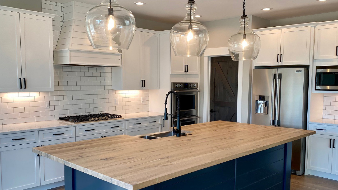 Modern Kitchen with pendant lamps and blue island