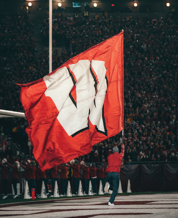 Wisconsin cheerleader running a Wisconsin flag down the end zone