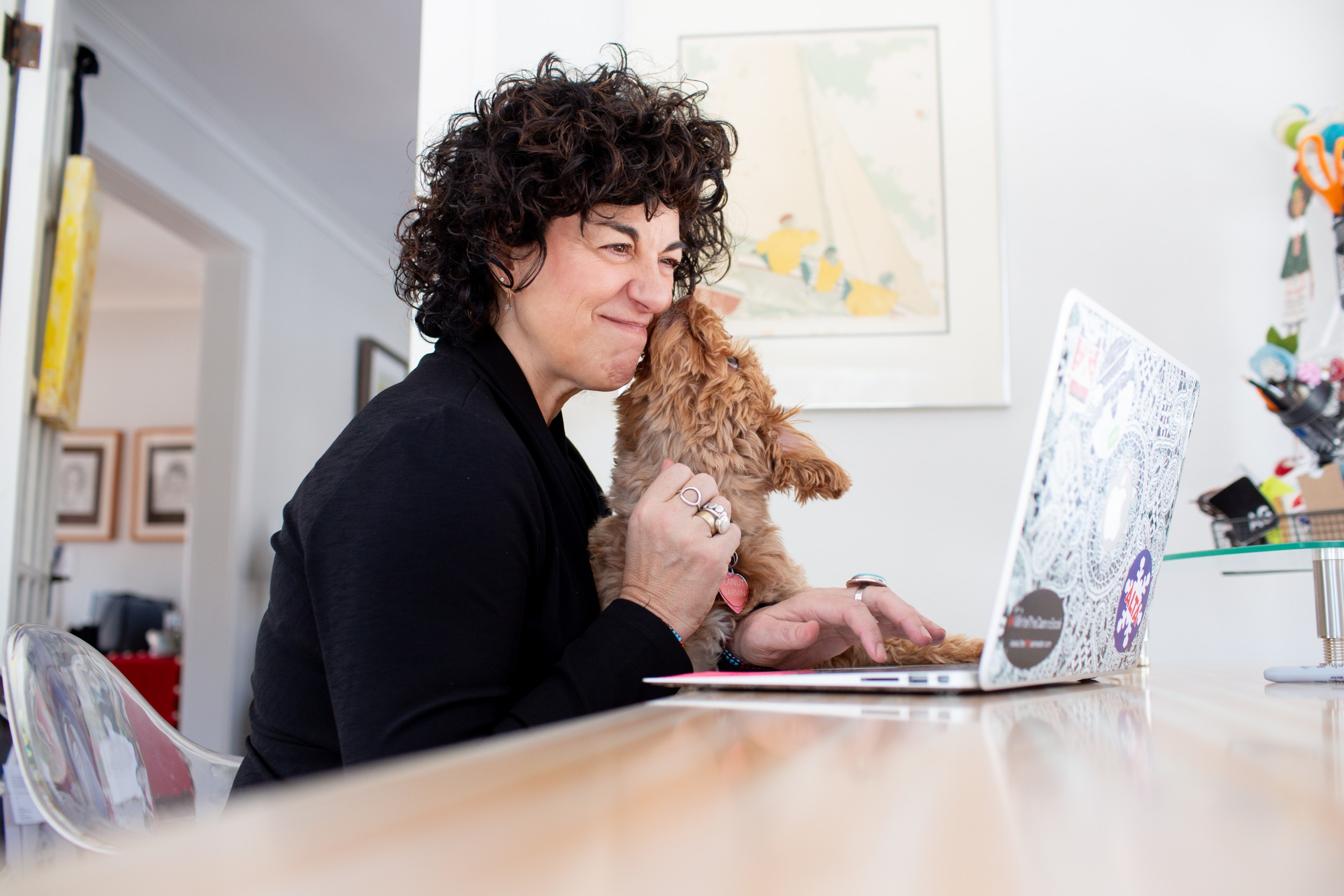 Ann Garvin is sitting at a table before her open laptop with her dog, Peanut, on her lap, who is giving her a smooch