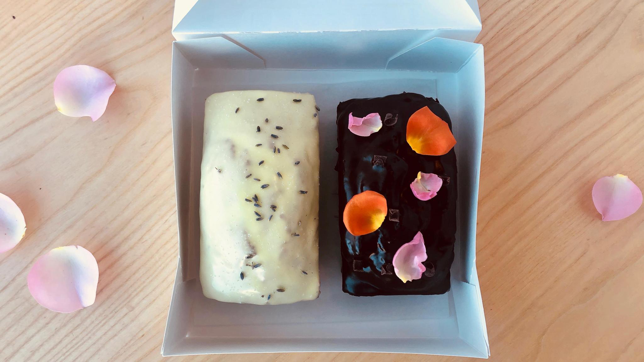 Two tea cakes in a box surrounded by flower petals.