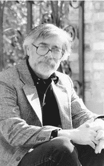 An older black and white photo of author Larry W. Phillips, wearing a jacket and glasses, seated with his hands folded.