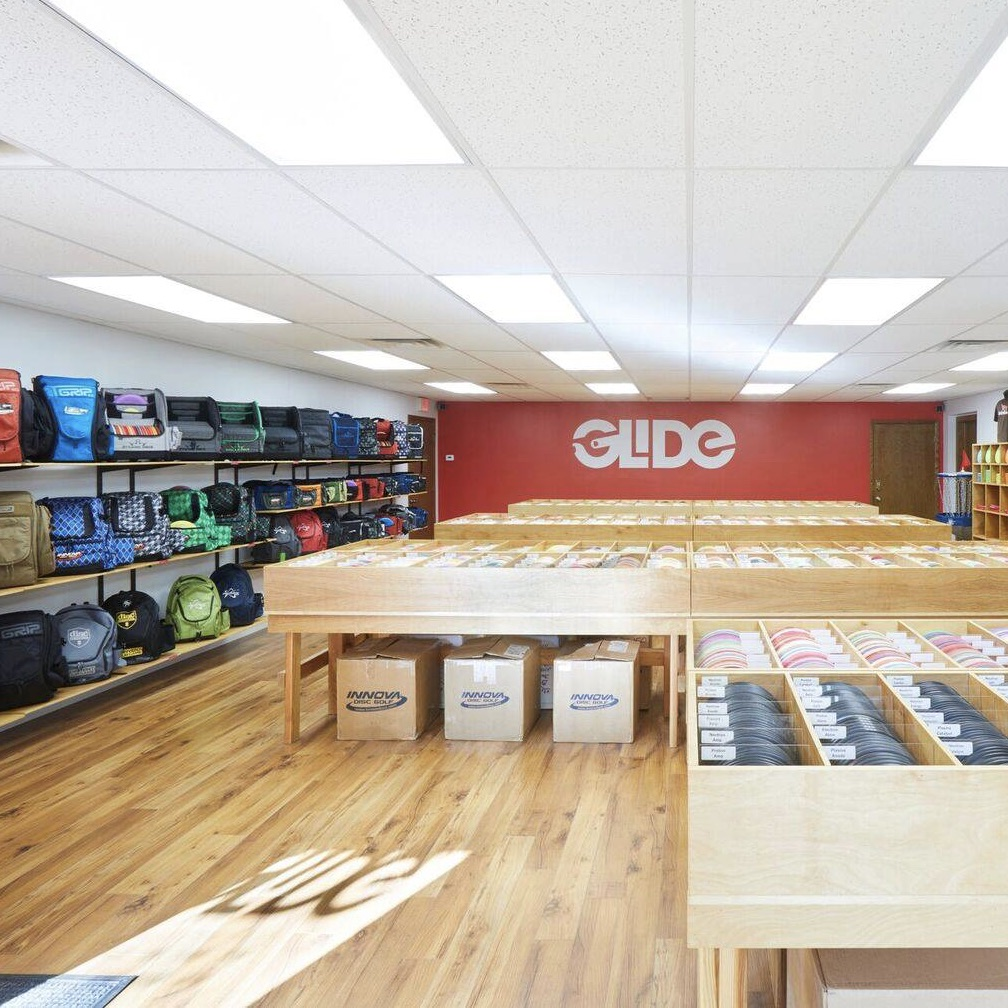 An interior short of the Glide disc golf store, with wood floors and long rows of various discs on display, plus shelving running the left wall that shows various bags.