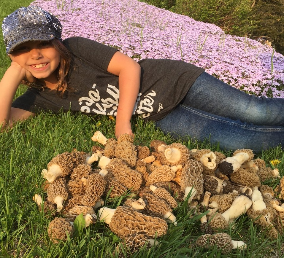 A young girl lies next to a pile of morel mushrooms in the grass at her family farm.