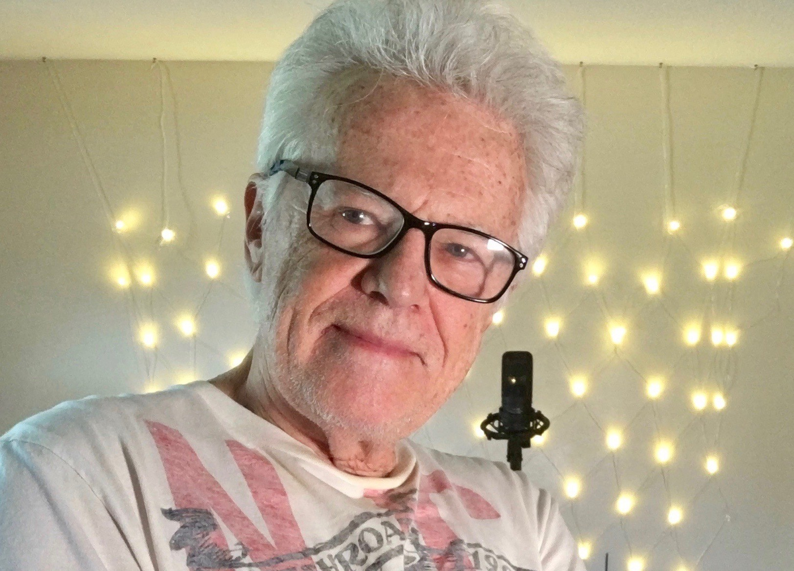 Al Craven Aka The White Raven in a tee shirt with silver hair and black glasses in a recent photo with twinkly lights behind him.