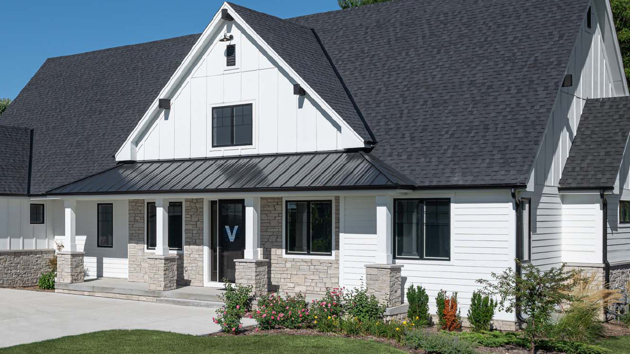 Modern white farmhouse with black roof and window frames