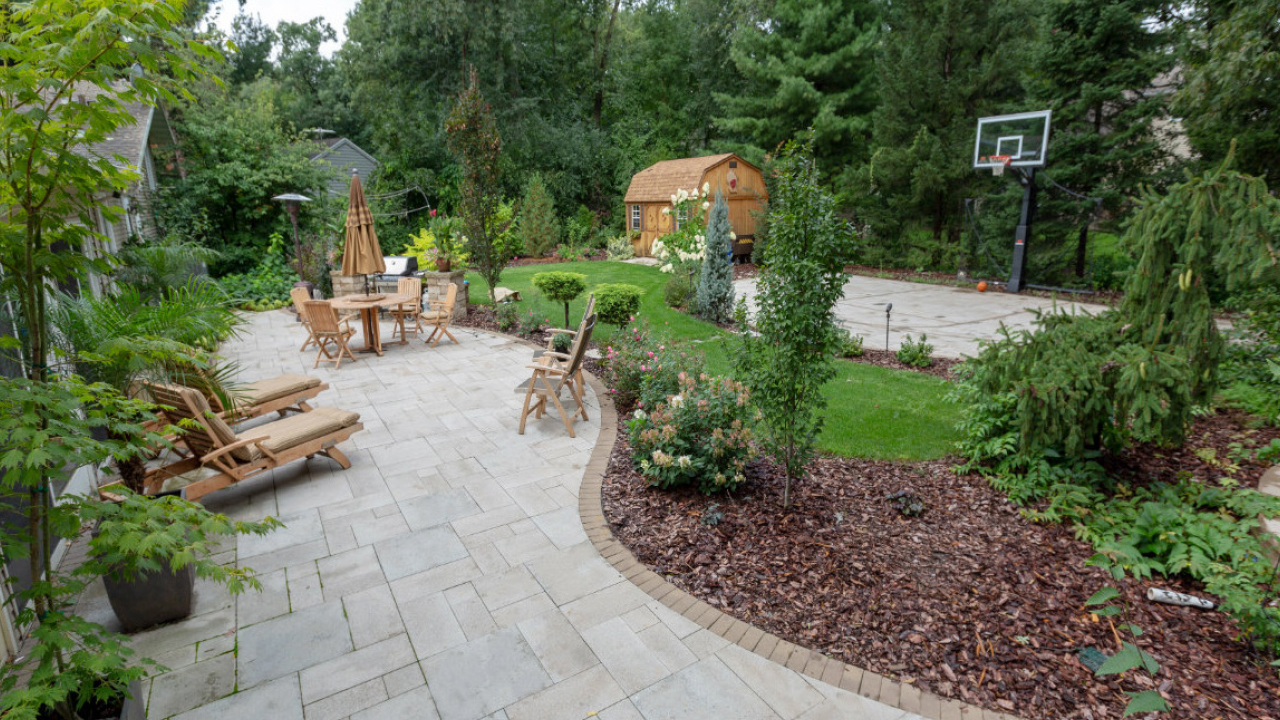 Outdoor brick patio with outdoor furniture and landscaping