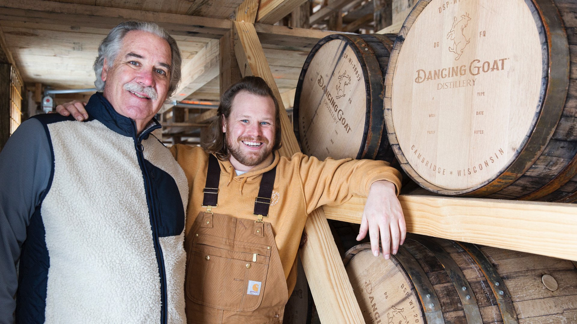 Two men stand in front of distilling barrels.