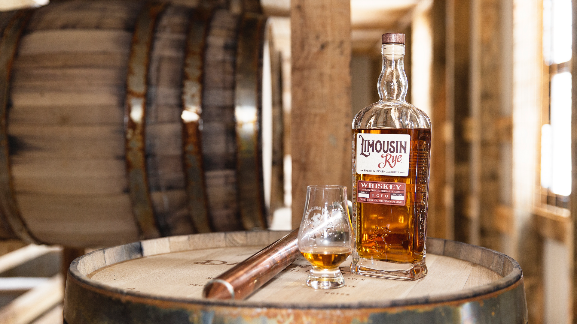 A bottle of Limousine Rye Whiskey and a glass stand on top of a distilling barrel.