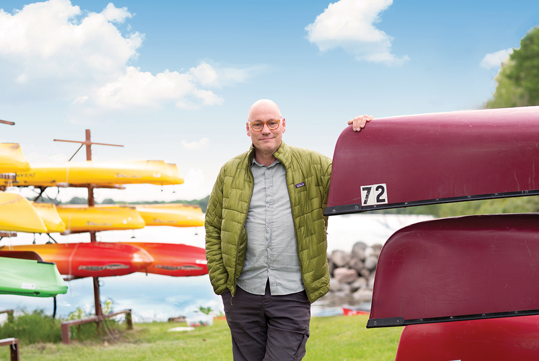Darren standing in front of canoes and kayaks