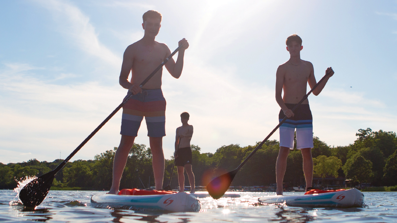 three boys standing on paddleboards