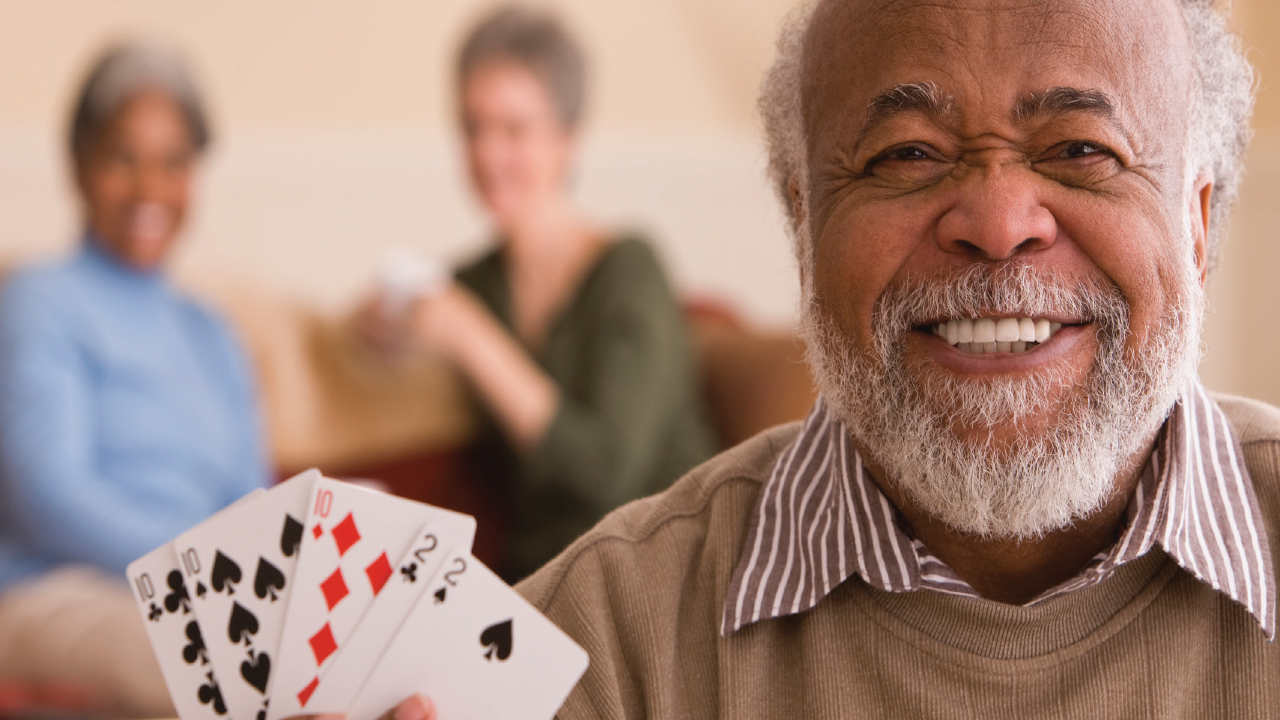 Elderly man playing cards with group smiling.