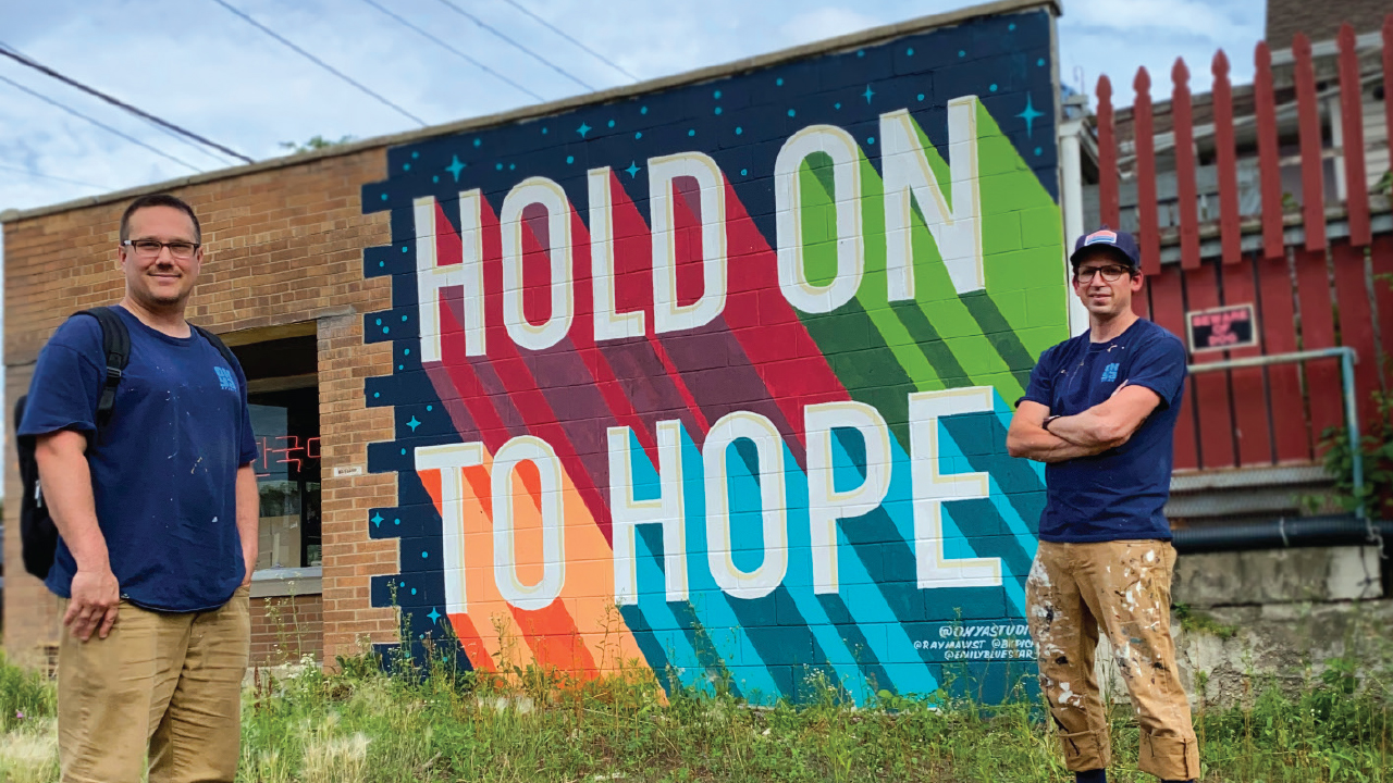 """two artists in front of the """"Hold On To Hope"""" Mural"""