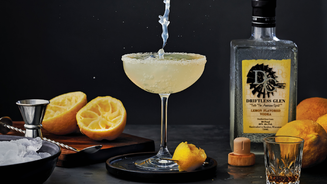 Lemon drop cocktail from Driftless Glen with a bottle of liquor and lemon garnishes around
