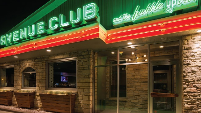 Exterior shot of the Avenue Club and the Bubble Up Bar with stone and glass exterior and neon and red sign.