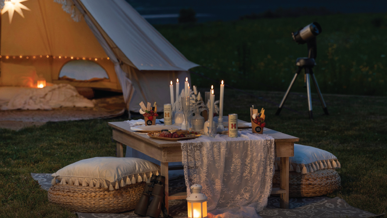 tent set up under the stars along with a table full of treats and drinks