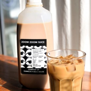 Zoom Zoom Juice in a half gallon container next to a glass