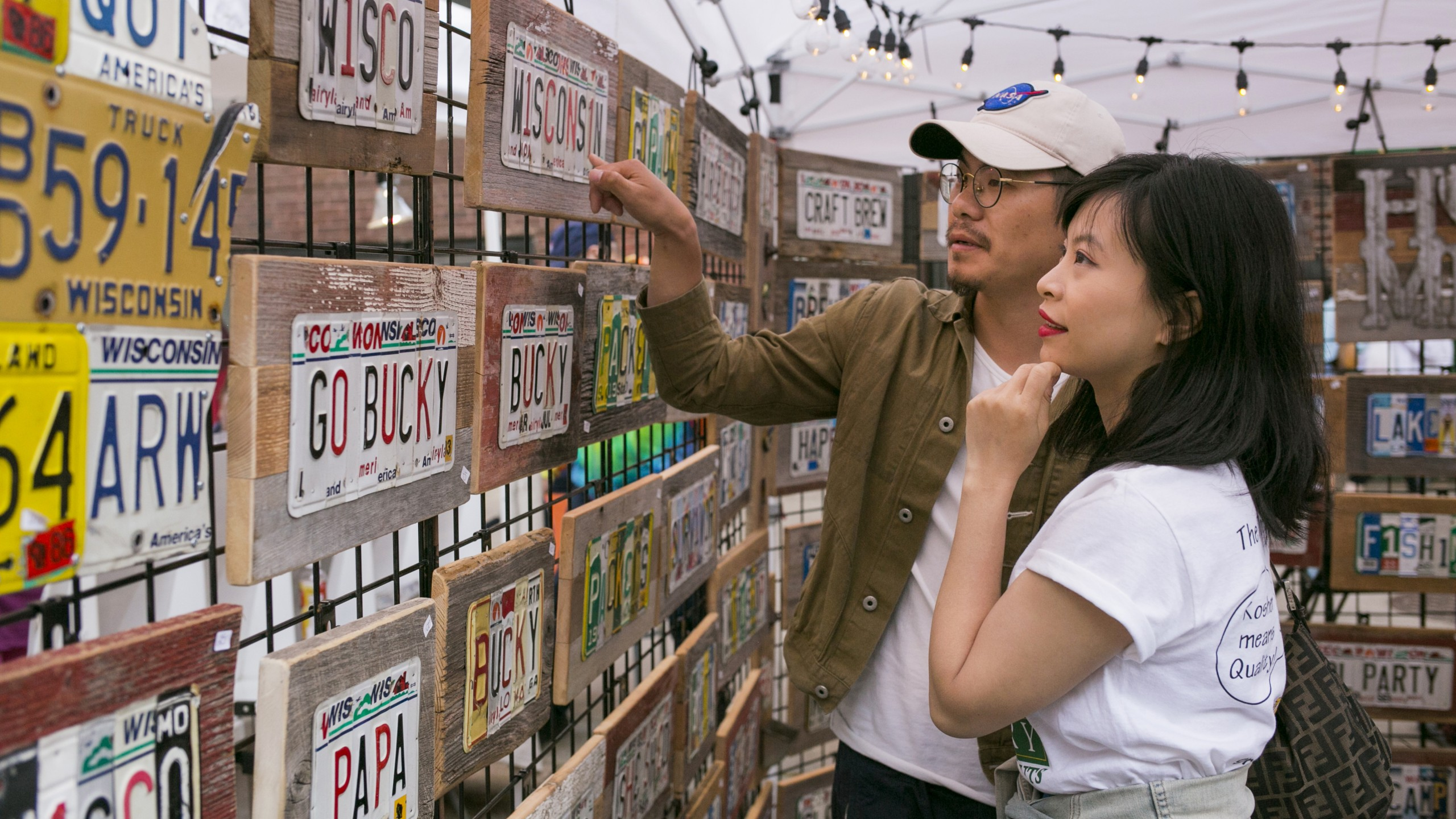 two people looking at license plate art at a Madison Night Market