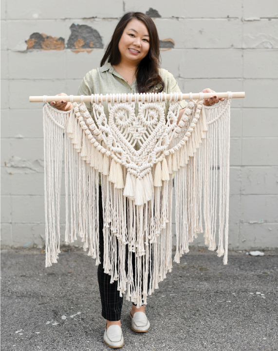 Maly Vang holding a large macrame wall hanging