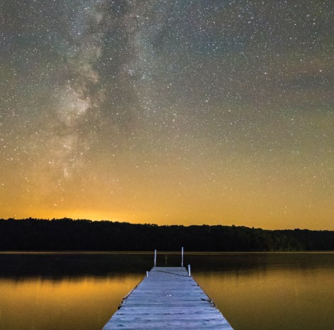 dock stretched out in the lake with stars above