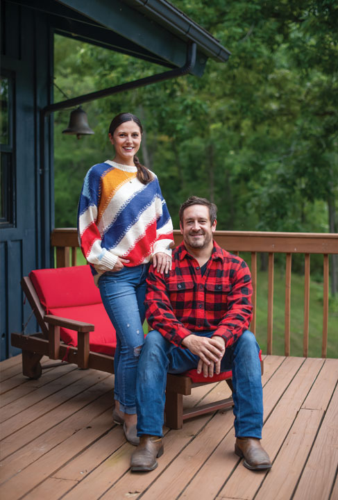 Simona and Jeremy Ebner sitting and standing on the deck
