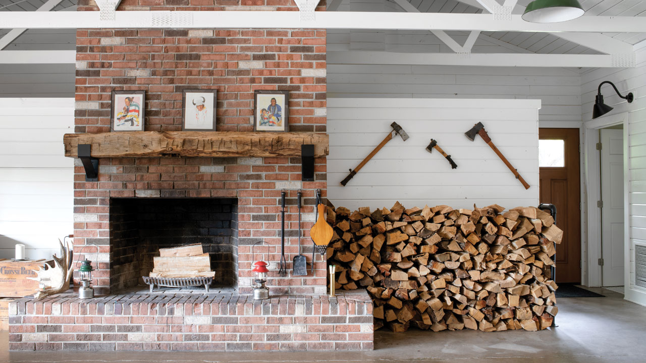 inside of the home with a big fireplace with wood stacked