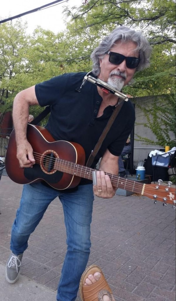 Robert J. is holding a guitar and has a harmonica around his neck. He is leaning forward in jeans and a black shirt and black sunglasses and his hair is long and silver with a silver goatee.