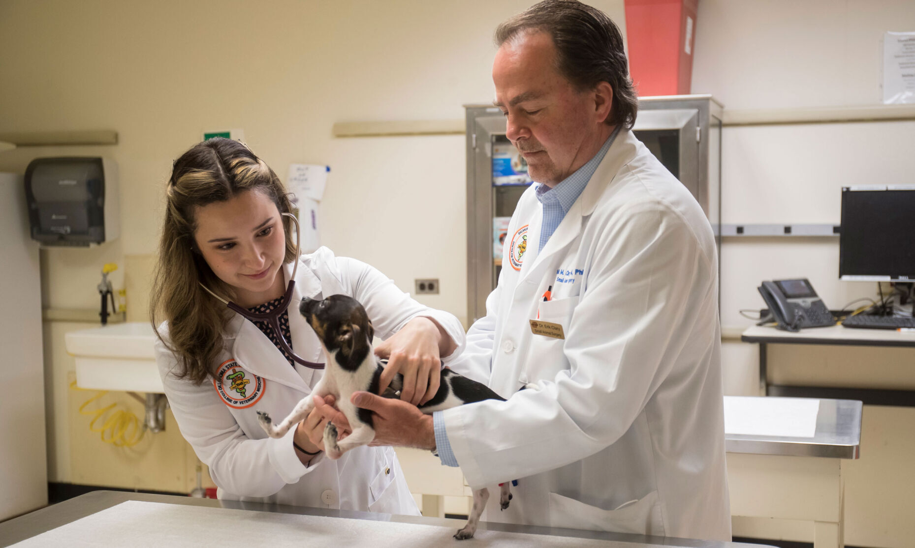 <p>Oklahoma State University fourth-year veterinary student Gabriela Iribar listens to Siggi's heart, along with Dr. Erik Clary, before the puppy's corrective surgery.</p>