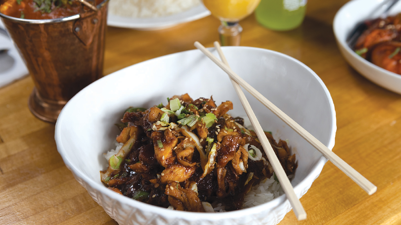 korean bbq chicken dish in a white bowl with chopsticks over rice